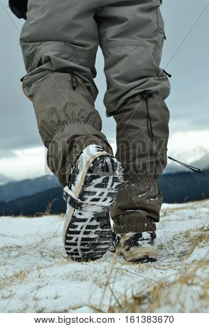 Man taking the step on a snowy mountain pick.