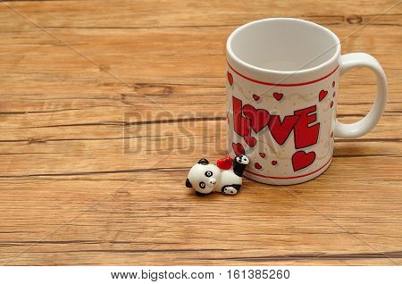 Valentine's Day. A white mug with the word love on it with a ceramic panda figurine holding a red heart