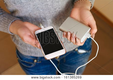 Two Girls Hands Hold Of The Phone And Charger. Powerbank And Smartphone In Girl's Hands. Energy Char