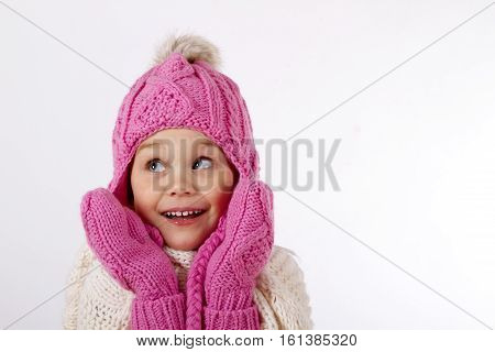 Pretty charming little girl in a knitted hat and a mittens. He is smiling and looking up. close-up portrait