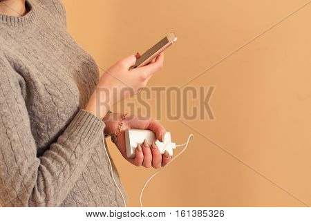 Charging Smart Phone With Power Bank On Yellow Background. Modern Digital Gadget. Girls Hands Hold N
