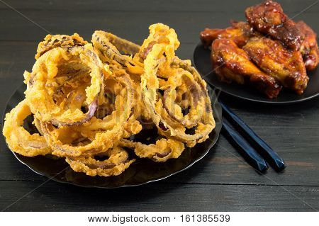 Onion Rings With Chopsticks And Bbq Chicken Wings