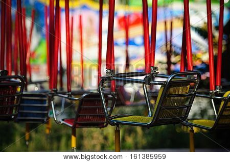the empty seats of the children's carousel in the Park