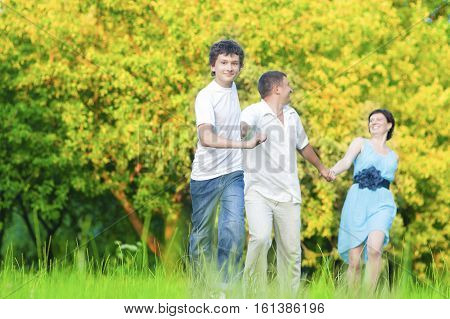 Family Values Concepts and Ideas. Caucasian Family of Three Having Fun Together and Running in Summer Forest With Joined Hands. Horizontal Image