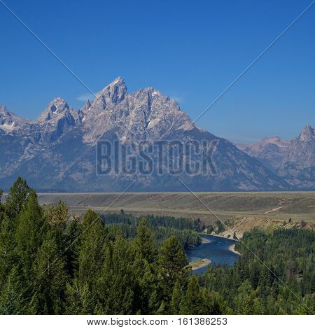 The Grand Teton Mountains on a summer day with jagged peaks and a forest river winding below.