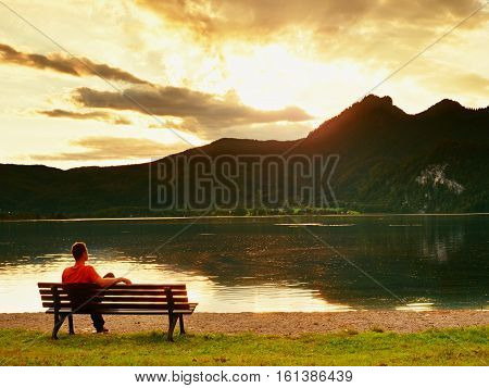 Alone man sits leg over on bench beside an azure mountain lake. Man relax and watch high peaks of Alps above lake mirror.