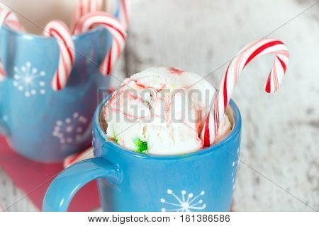 Peppermint ice cream with candy canes in a blue holiday cup