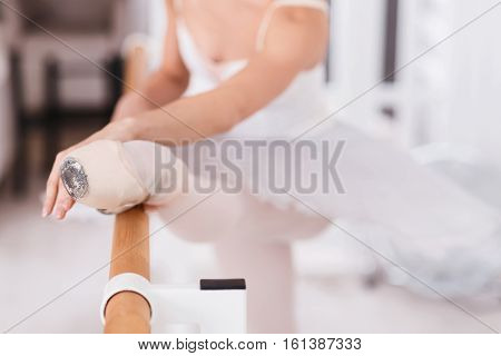 Ballet in details. Leg in ballet points of young woman wearing the leotard with white tutu keeping her hands on the ballet bar while stretching her leg