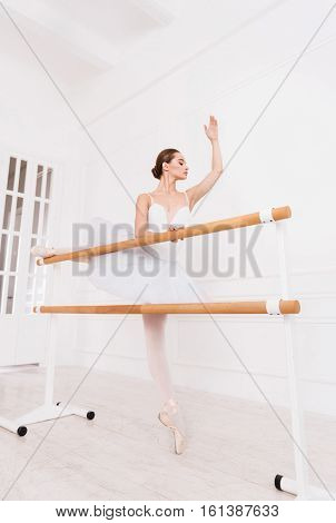 Rehearsal before performance. Delicate young brunette doing ballet poses and stretching exercises using ballet bar in studio