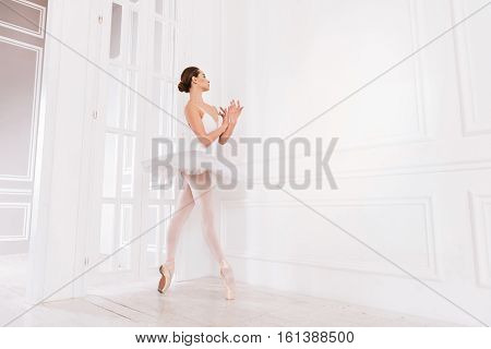 With love. Elegant beautiful classical dancer wearing white leotard with fluffy skirt and points keeping her arms crossed on chest while standing in semi position