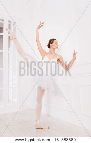 Ballet poses. Elegant ballet dancer wearing beige points and white leotard with tutu stretching her leg while holding her arm in the air