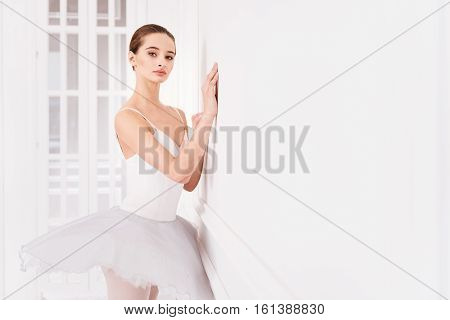 Place for training. Graceful brunette with bun on the head wearing leotard with fluffy skirt keeping her arms on the wall while posing in dance studio