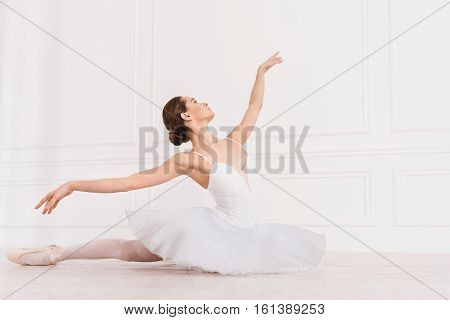 I fly. Delighted cheerful girl sitting on the floor with straight leg keeping her hands in the air while looking sideways