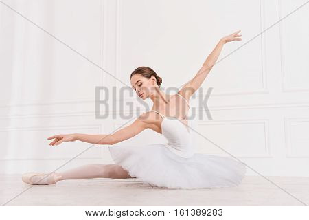 Follow my example. Serious young ballerina wearing white leotard with fluffy skirt looking down while stretching her leg on the floor