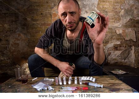 Drug dealer showing money received from selling drugs and narcotics. Many types of narcotics or drugs represented in front of him on table.