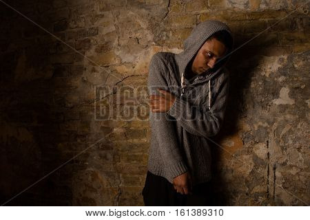 Drug abuse concept. Overdose of Asian male. Drugs narcotic syringe in action. Man posing near brick wall.