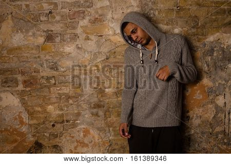 Addict, breaking, pain, depression, drama, and dependence - result of narcotics . Drug addict posing near brick wall