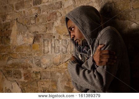 Drug addict posing near brick wall. Addicted, breaking, pain, depression, drama, illness, dependence Ill person hugging himself
