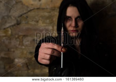 Bad woman. Addict lady with syringe using drugs. Drug addict woman holding syringe with drugs in front of her.