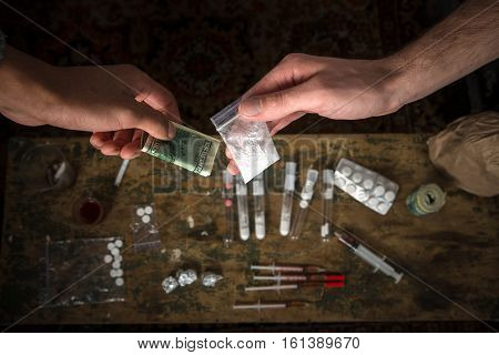 Purchase, possession and sale of drugs is punishable by law. Many types of narcotics and drugs represented on table.