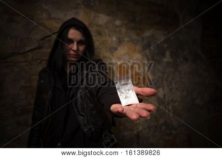 Drug addict do not know how to get rid of drug addiction. Drug addict holding narcotics or drugs and showing it to camera.