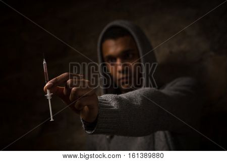 Drug addict holding syringe with drugs in front of him. Drugs concept. Disease concept. Drug addict man with syringe using drugs.