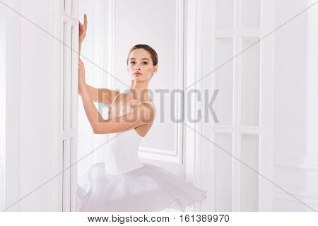 My lifestyle. Graceful young female looking at camera wearing white short dress while posing in the doorway