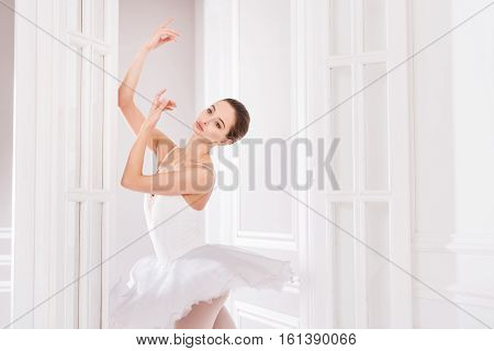 Guessing future. Elegant ballerina wearing white leotard with fluffy skirt looking sideways while standing in the doorway