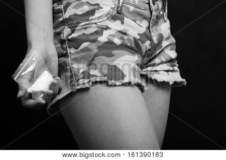 hand with a bag of drugs at a pocket monochrome image