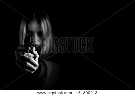 serious girl with gun aiming on black background with copyspace, monochrome