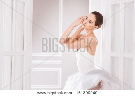 Warmth in photo. Graceful cute ballerina touching her face looking sideways while standing in the ballet studio