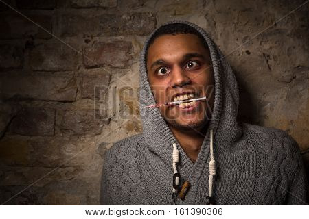 Addict Asian man caught buzz. Drug addict man holding syringe in his mouth isolated on brick background on street.