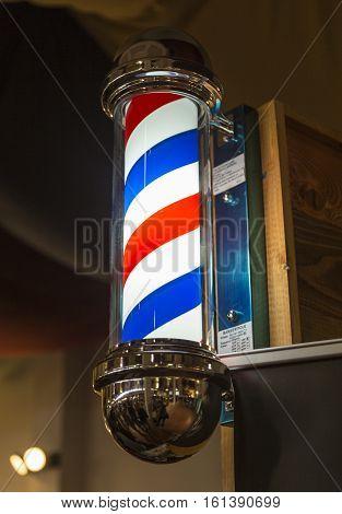 A beautiful barber shop pole light on a brick.