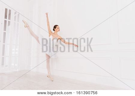 New position. Serious ballerina looking at her hand wearing white leotard with tutu while posing in dance studio