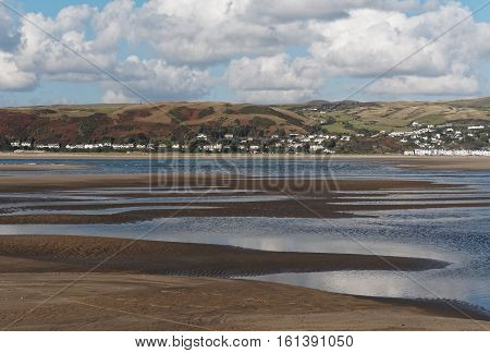 Beach and sea at low tide at Aberdovey a beautiful little village on the sea at the southern tip of the Snowdonia National Park Gwynedd Wales.