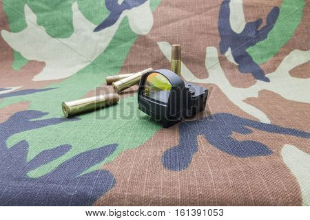 Collimator sight and bullets on camouflage background side view. poster