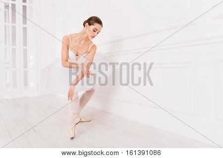My hobby. Graceful female wearing white leotard with tutu while standing in ballet position holding right hand bent in elbow over left hand