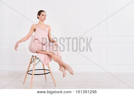 I am always serious. Supercilious young female wearing pink dress looking straight at camera keeping her legs straight while posing on the chair