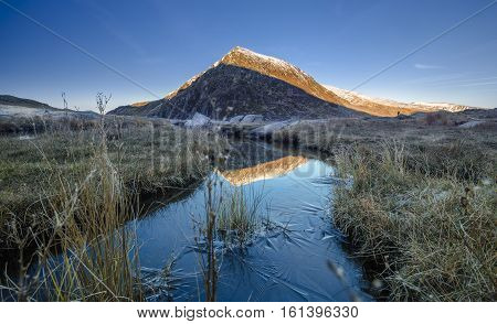 Frozen Creek and Snowy Summit in Snowdonia National Park UK