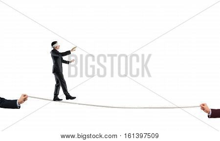 Concept of risk and danger with businessman isolated on white balancing on rope