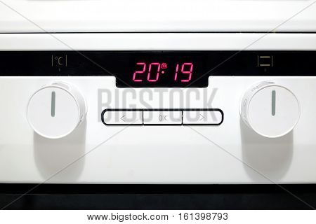 Control panel with red digits on electronic timer display, buttons and round knobs on modern white kitchen electric stove front view closeup