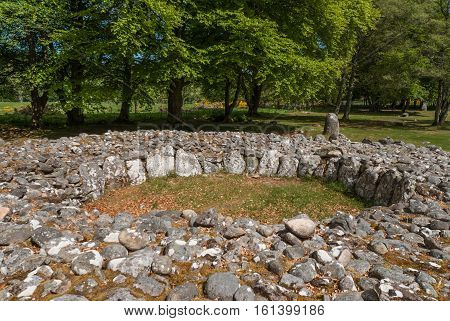 Inverness Scotland - June 2 2012: Grave site heap of gray stones at prehistoric Clava Cairns. Stones form circle. Surrounded by green trees and grassy field. Bird's eye view.