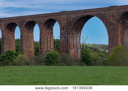 Inverness Scotland - June 2 2012: Section of red stone Culloden train viaduct with widest bow over Nairm River. Green meadows up front blue sky forests behind bridge. Water discoloring of walls.