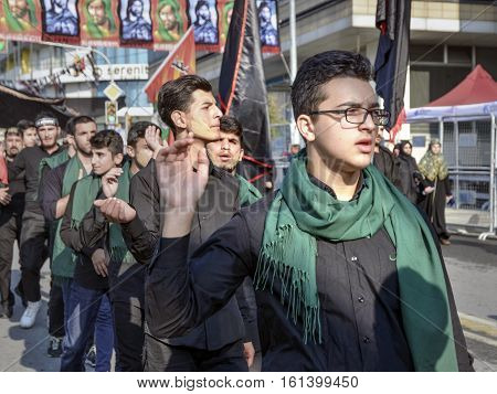 Istanbul Turkey - October 11 2016: Shia Muslim men shout Islamic slogans as they mourn during an Ashura procession. Muslims worldwide marks Ashura Istanbul Shiite community. Mood chronology to adapt to his faces hair and clothes muddy. The battle of Karba
