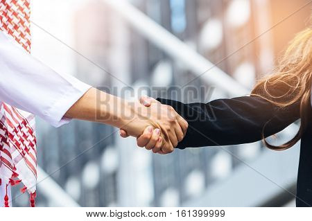 Business success concept. Asian muslim businessman and Engineer woman making handshake or holding hand together to agree joint business and partnership.