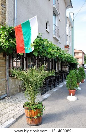 An outdoor cafe on a street in Bulgaria. Flag.