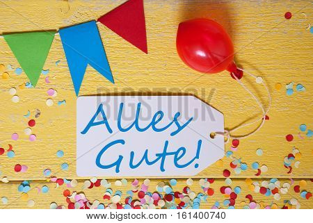 White Label With German Text Alles Gute Means Best Wishes. Party Decoration Like Streamer, Confetti And Balloon. Flat Lay Or Top View. Yellow Wooden Background