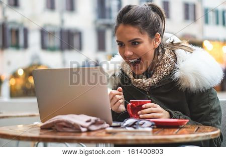 Beautiful girl student checking her exam results on the computer in a bar drinking coffee - Stunning young woman on her computer in a bar in city center drinks coffee while shopping online