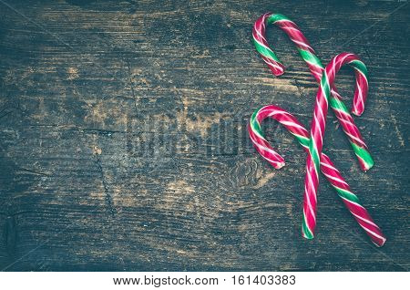 Striped Christmas candy canes on shabby chic wooden background with place for text. Red and green candy canes on weathered wooden board. Christmas Background. New Year Background. Copy space.