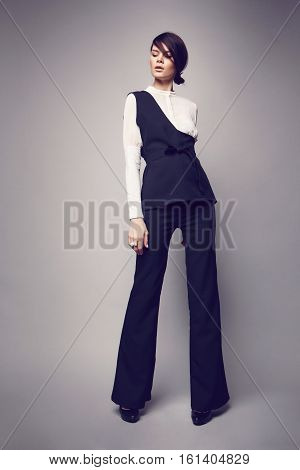 Fashionable woman in sleeveless jacket in studio